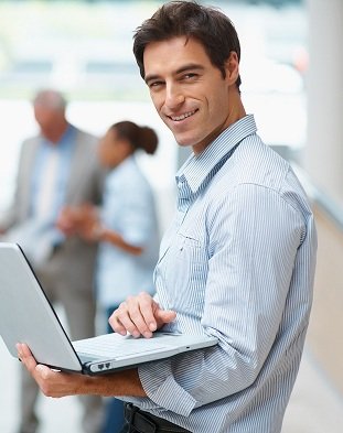 Young business man using laptop with colleagues at the back