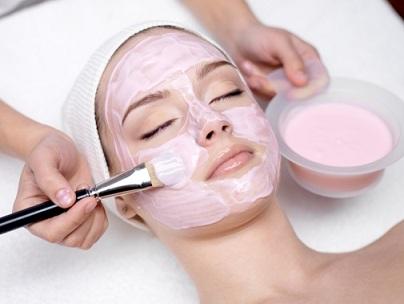 Girl receiving cosmetic pink facial mask